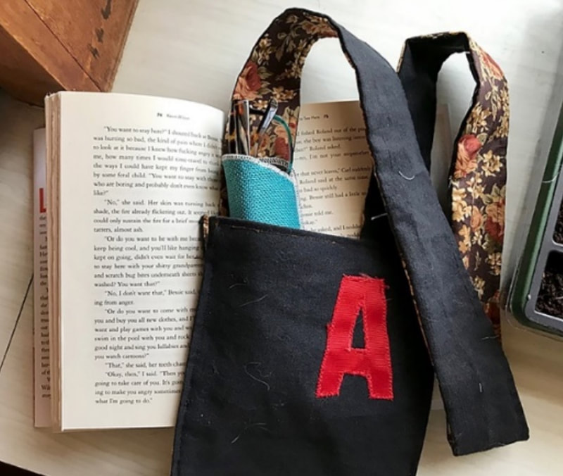 a black fabric shoulder bag decorated with a red letter A, displayed with an open copy of the Scarlet Letter