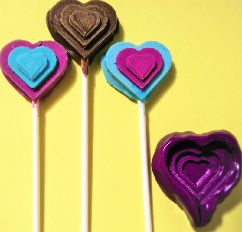 the mold, cast, and replicas of a heart-shaped chocolate lollipop