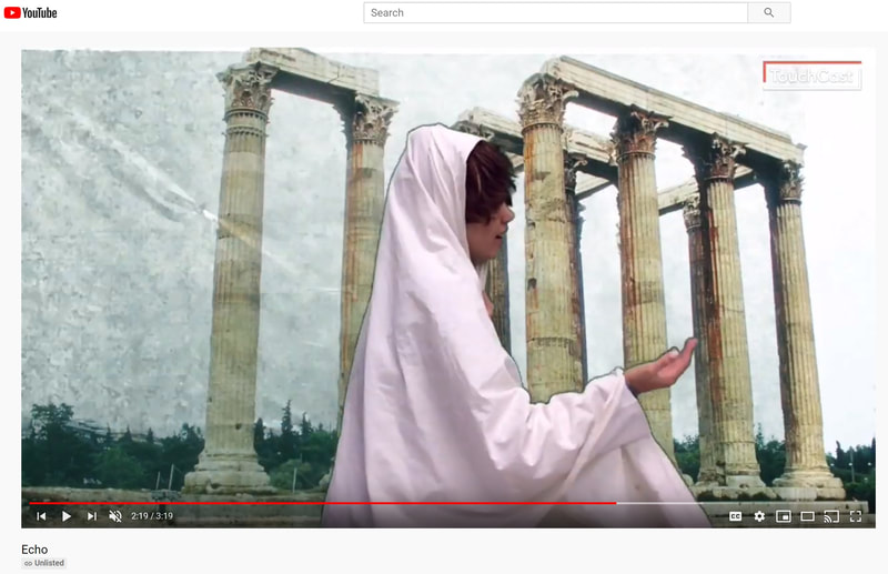 screenshot of a student costumed in a robe against a greenscreened backdrop of Greek-style columns