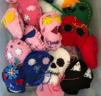 hand-sewn plush skulls in a variety of colors