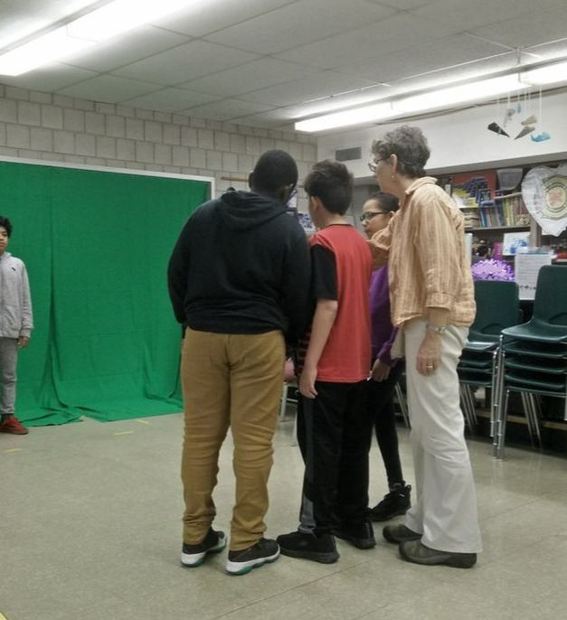 3 students and a teacher cluster around a camera, shooting a 4th student against a green screen