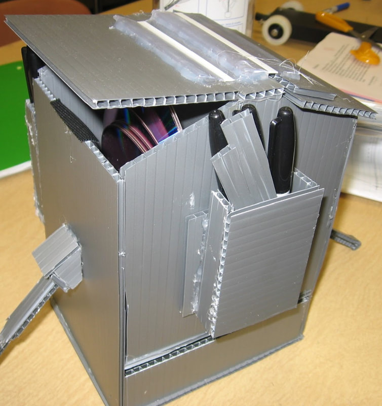 an office-supply organizing caddy made from corrugated plastic, holding sheets of craft material and markers