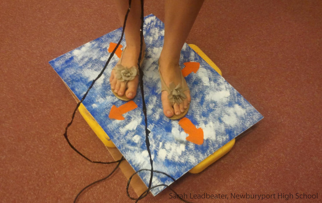 the feet of a student standing on a video game control pad
