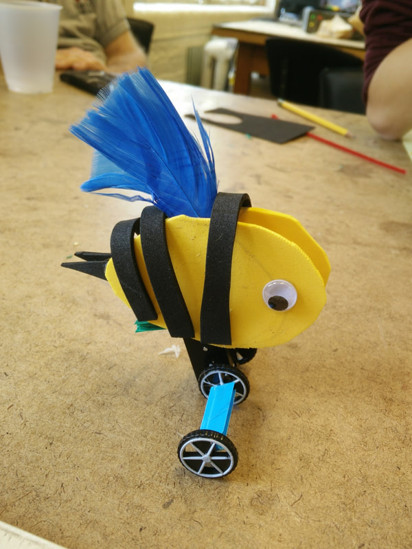 a custom-built wind-up toy topped with a bee-like, googly-eyed creature