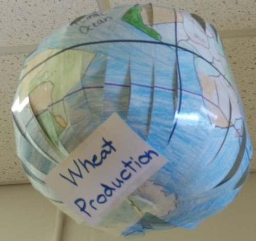 "a paper globe marked with a sign reading ""wheat production"" and maps marked to show major wheat producing regions"